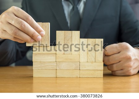Businessman make a building with wood blocks