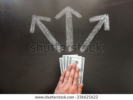 businessman making a decision for their money  in front of three arrows showing different ways - stock photo