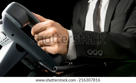 Businessman making a telephone call holding the handset receiver of a landline instrument in his hand , close up view of his hand in a suit. - stock photo