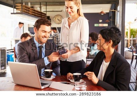 Businessman making contactless card payment in a cafe - stock photo