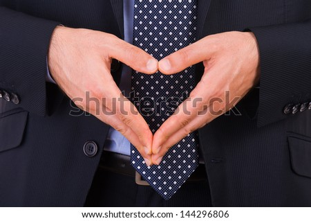 Businessman making heart symbol with hands. - stock photo