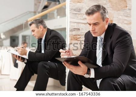 Businessman making notes. Confident mature man in formalwear making notes in his note pad while sitting on staircase  - stock photo