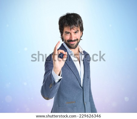 Businessman making Ok sign over blue background