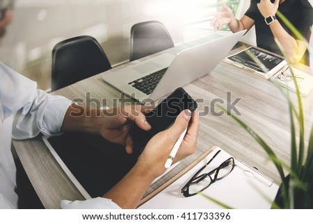 Businessman making presentation and using smart phone with his colleagues and business strategy digital layer effect at the office as concept - stock photo