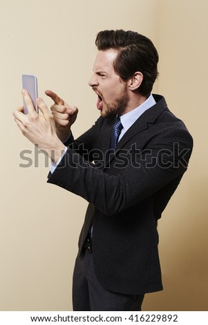 Businessman making threatening phone call - stock photo
