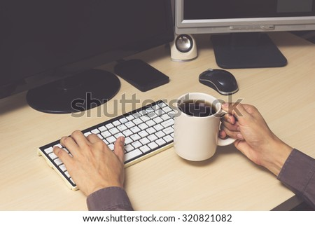businessman, male employee hands with computer & cup of coffee on workspace desk in office