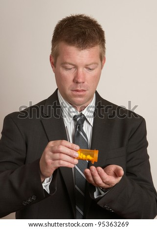 Businessman man in suit taking drugs from pill bottle - stock photo