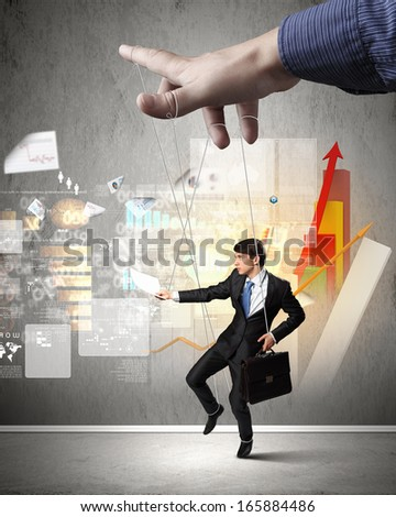 Businessman marionette on ropes controlled by puppeteer against diagram picture - stock photo