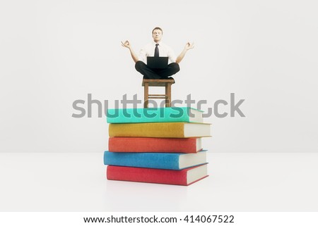 Businessman meditating on colorful book stack. 3D Rendering - stock photo