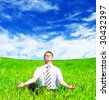 Businessman meditating on the meadow under blue sky - stock photo