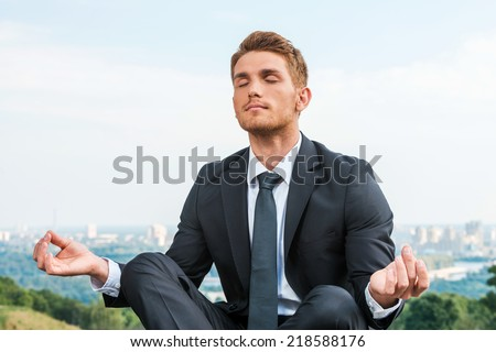 Businessman meditating. Relaxed young man in formalwear meditating while sitting in lotus position with cityscape in the background - stock photo