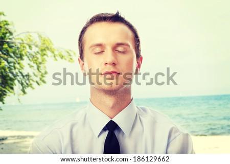 Businessman meditatink at the beach. - stock photo