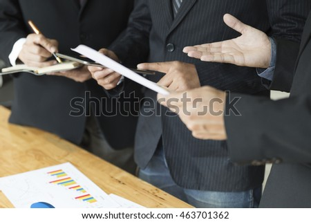 businessman meeting, analyzing and discussing with tablet and paperwork document