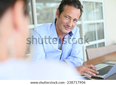 Businessman meeting client in office - stock photo