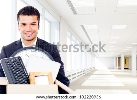 Businessman moving into a new office holding a box - stock photo