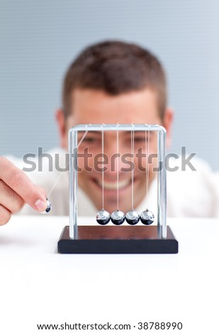 Businessman moving Newton balls in office - stock photo