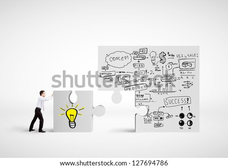 businessman moving puzzle with drawing business plan - stock photo