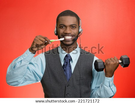 Businessman multitasking. Portrait corporate business man talking on phone, brushing teeth, lifting dumbbell isolated red background. Positive face expression, emotion. Phone addiction concept - stock photo