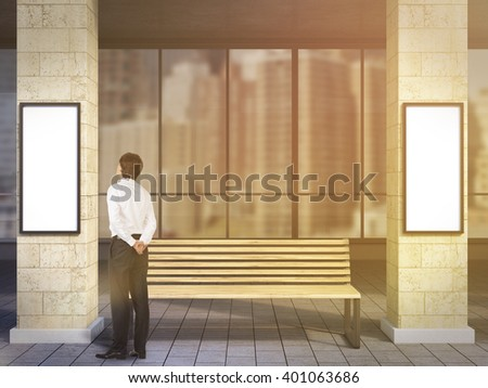 Businessman near bench under portico between columns looking at blank poster. Toned, filter. Concept of waiting at bus stop. - stock photo