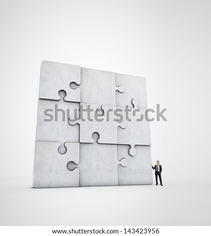 businessman near concrete jigsaw puzzle - stock photo