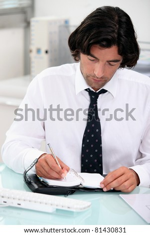 Businessman noting appointment on organizer - stock photo