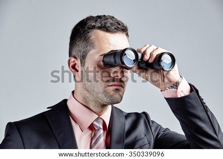 Businessman observing with binoculars isolated over grey - stock photo