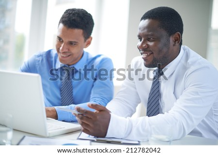 Businessman of African-american ethnicity pointing at laptop screen during presentation - stock photo