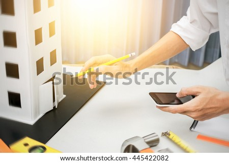 Businessman of architect engineering checking a tower model project management planning for risk and strategy of architecture design, close up shot with vintage tone and sunlight effect. - stock photo