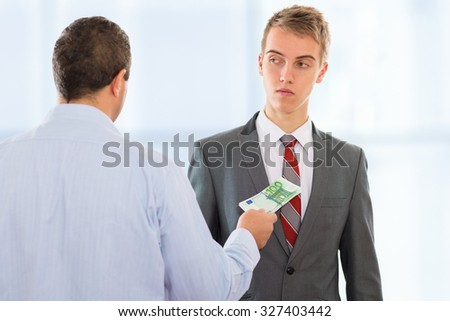 Businessman offering bribe money to another businessman that is hesitant to accept it - stock photo