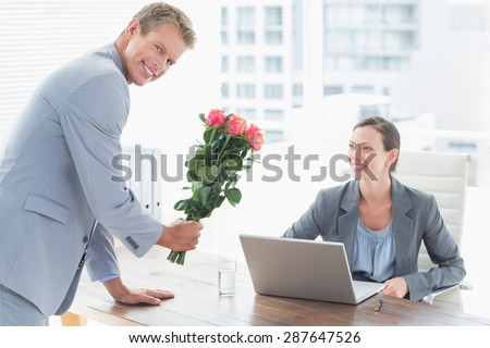 Businessman offering flowers to his colleague in an office - stock photo