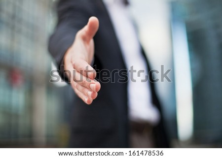 Businessman offering for handshake on office buildings background