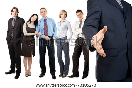 Businessman offering for handshake with colleagues standing in the background - stock photo