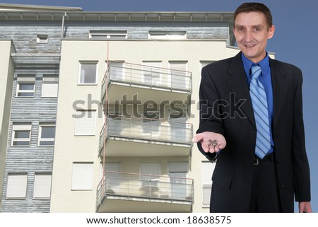 businessman offering key for a flat in this house - stock photo