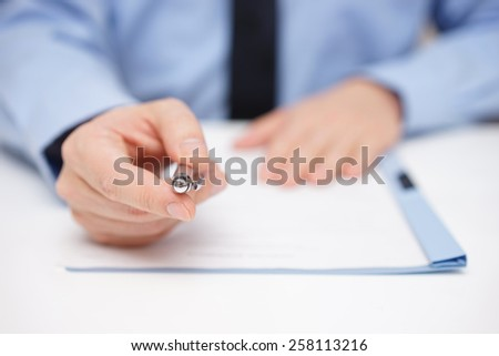 Businessman offering pen to sign - stock photo