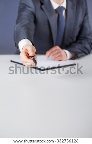 Businessman offering to sign a document, blue background
