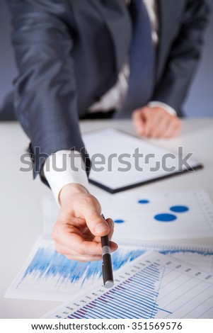 Businessman offering to sign a document, blue background - stock photo