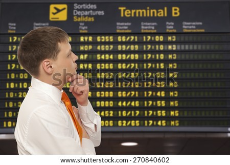 Businessman on a background of departure board at airport - stock photo