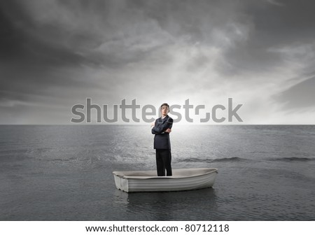 Businessman on a boat in the middle of the sea - stock photo
