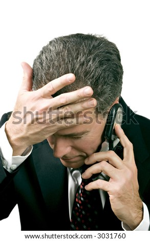 Businessman on a cell phone reacting in a distressed manner to what is being said during a phone conversation. - stock photo