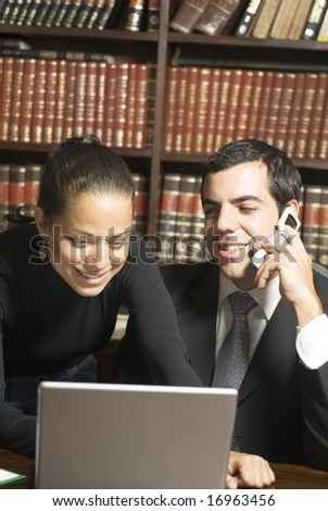 businessman on a cellphone and woman looking at a laptop. Vertically framed photo. - stock photo