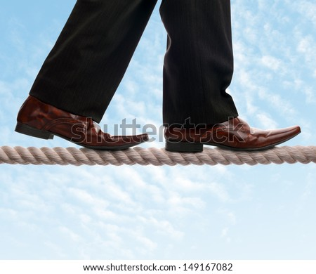 Businessman on a tightrope concept for risk, balance, leadership and conquering adversity - stock photo