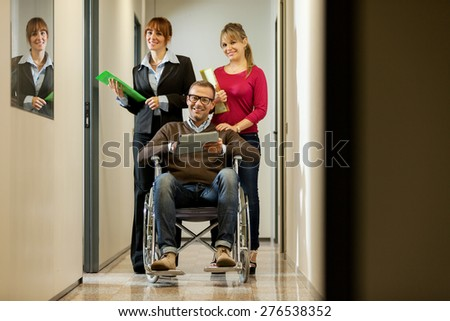 Businessman on a wheelchair with his colleagues in the corridor - stock photo