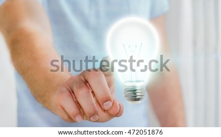 Businessman on blurred background touching shiny lightbulb with his finger â??3D renderingâ??