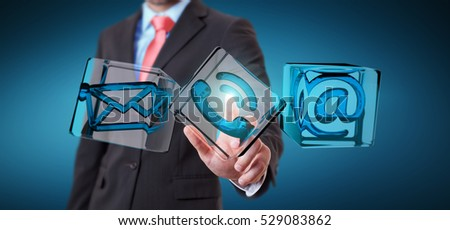 Businessman on blurred background touching transparent cube contact icon with his finger 3D rendering