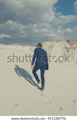 Businessman on desert dune. Rear view of young man in formalwear rising up by sand mountain