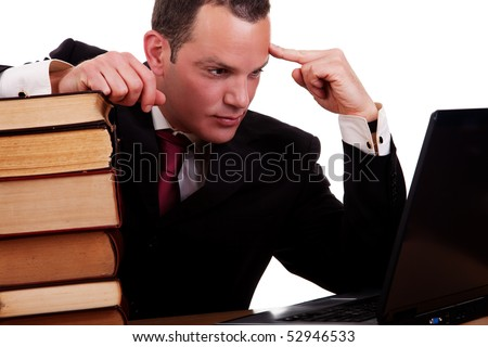 businessman on desk with books, looking at the computer, isolated on white background, studio shot. - stock photo