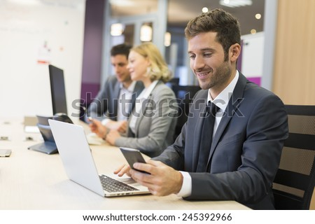 Businessman on mobile phone in office, sms, message - stock photo