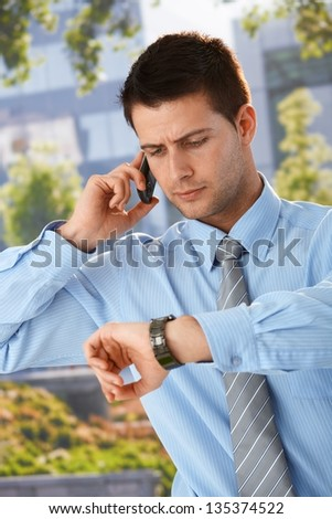 Businessman on phone call checking time on watch, looking worried, standing outside of office. - stock photo