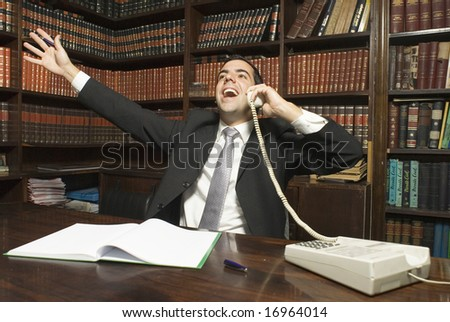 Businessman on phone is jubilant with his arms up in the air. Horizontally framed photo. - stock photo