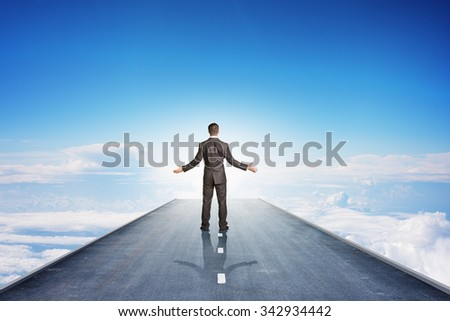 Businessman on road in sky, rear view - stock photo